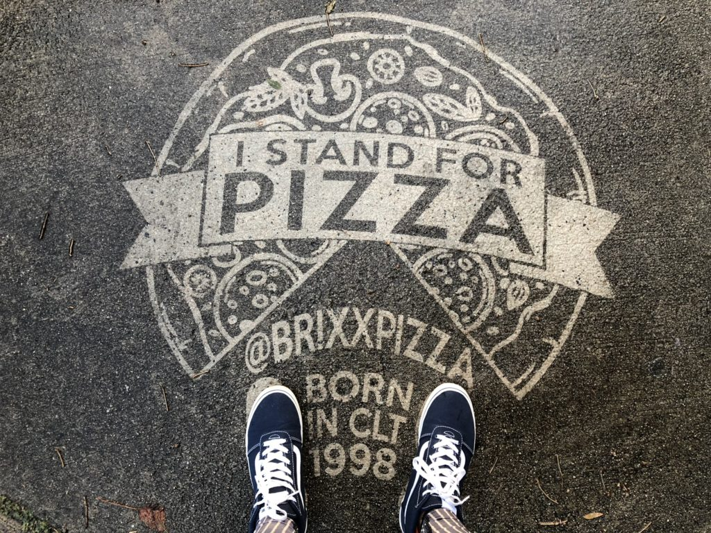 reverse graffiti of a pizza on the sidewalk for Brixx Pizza