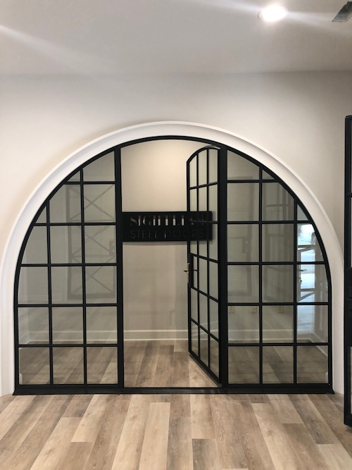 A glass and steel framed door that is perfectly arched.