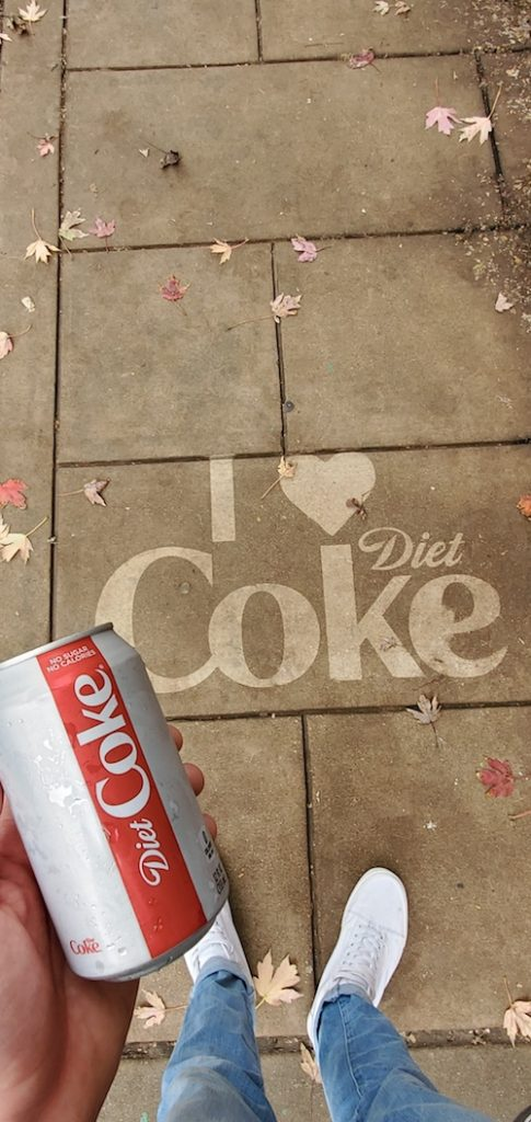 "Young person holding a Diet Coke in front of a pressure washed ""I heart Diet Coke"" ad on the sidewalk"